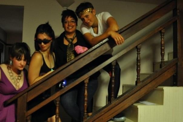 four women are lined up against a railing of staircase, preparing to go to a queer dance party.