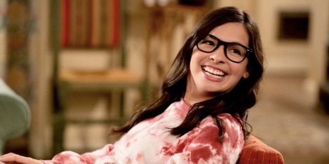 Elena Alvarez is getting hyped about watching One Day at a Time on CBS. She smiles the biggest dork smile and has on a tie-dye pink shirt.