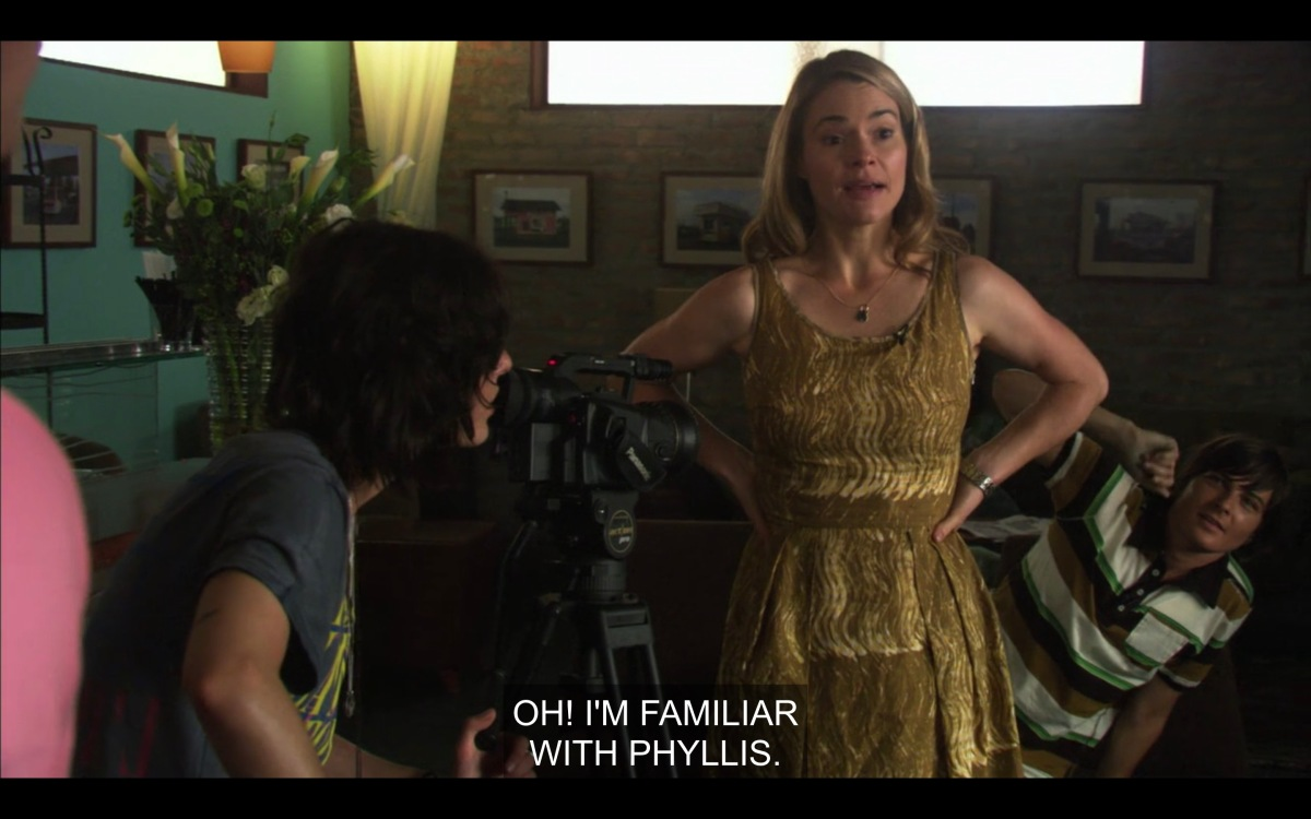 "Alice in a gold lame dress at The Planet, hands on hips, saying ""Oh, I'm familiar with Phyllis"""