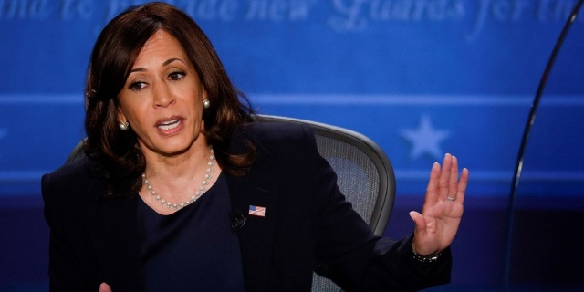 A still frame of Kamala Harris during last night's debate, seated in front of a blue backdrop and mid-sentence as she gestures to the side.