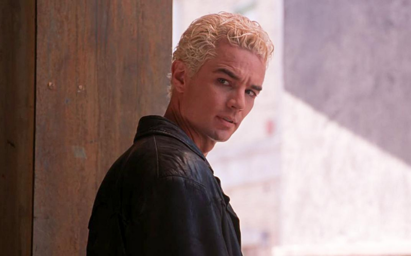 A bleach blonde man in a black leather jacket turns over his shoulder.