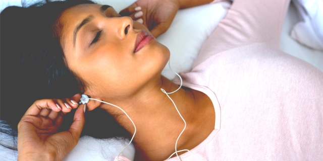 A South Asian woman in a pink sweater listens to music on her headphones, her mind at peace.