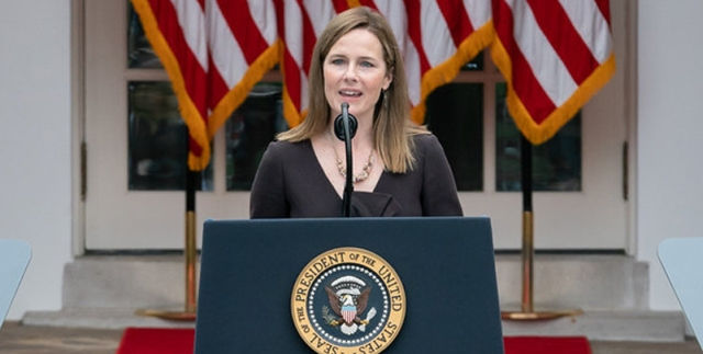 amy coney barrett, a white woman with shoulder length brown hair, stands in front of a podium, with a back drop of american flags behind her. her mouth is open and her eyes are squinting as she speaks.