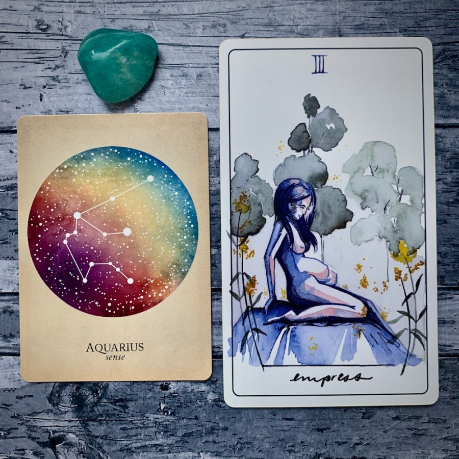 the Aquarius card from the Constellations deck and the Strength card