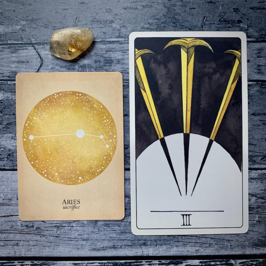 An Aries card from the Constellations tarot along with a Three of Swords