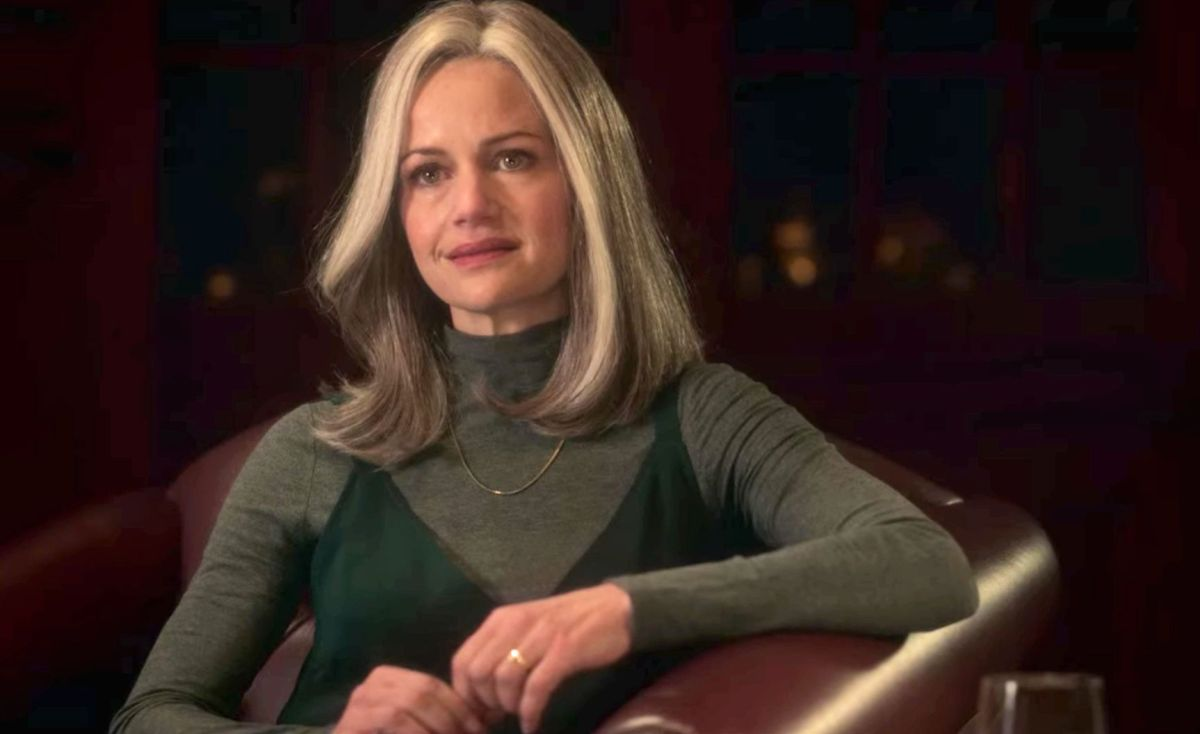 Carla Gugino wearing a gray wig and reclining in a chair during her appearance in Haunting of Bly Manor