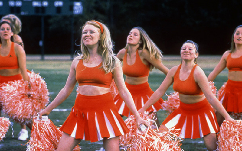 A group of cheerleaders in red-orange uniforms with pom poms cheer.