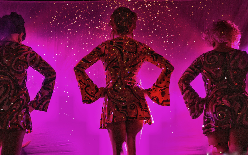 Three drag queens in sequin dresses stand with their backs turned in pink lighting.