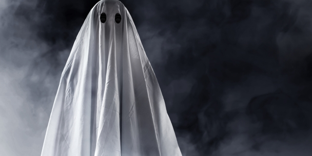 A white ghost floats in fog in front of a black background