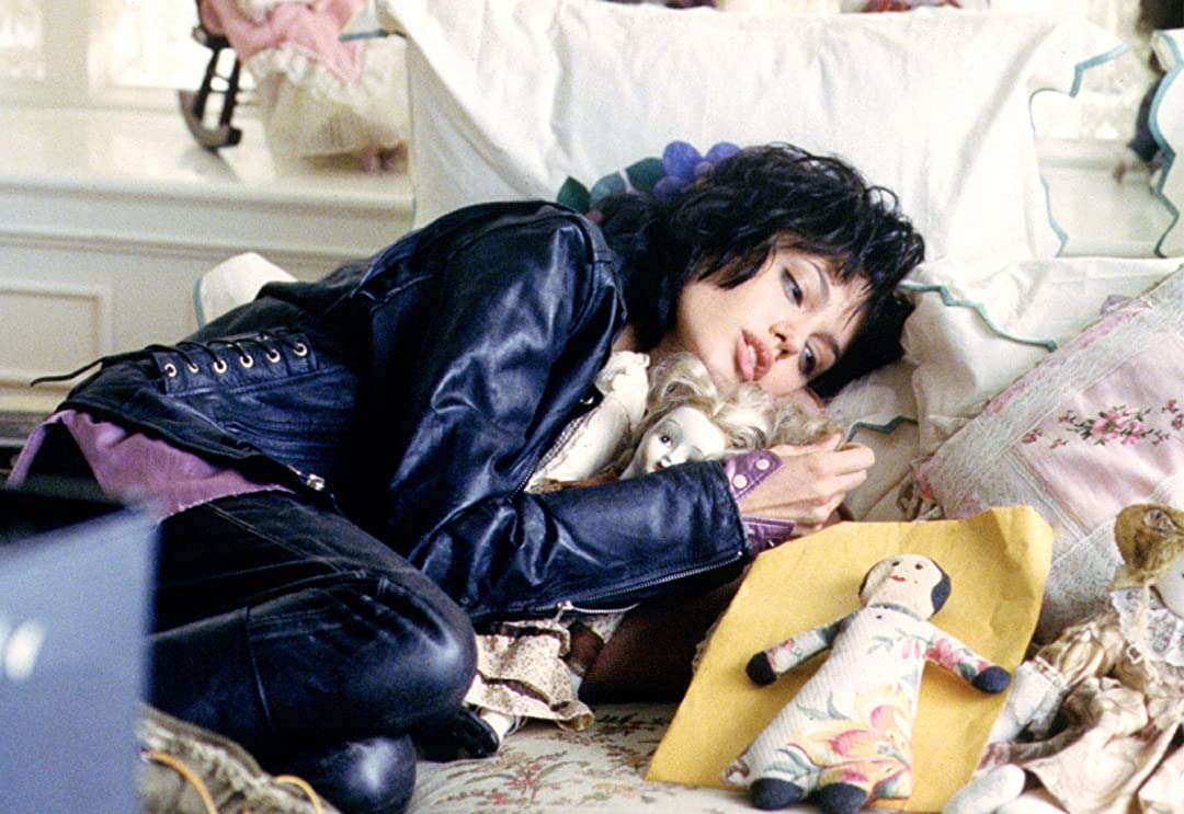 "still of angelina jolie playing Gia in ""Gia"", wearing a leather jacket and looking longingly at some dolls"