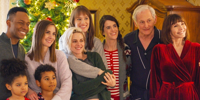 A still from Happiest Season with Mackenzie Davis' arm around Kristen Stewart with her family in front of the Christmas tree