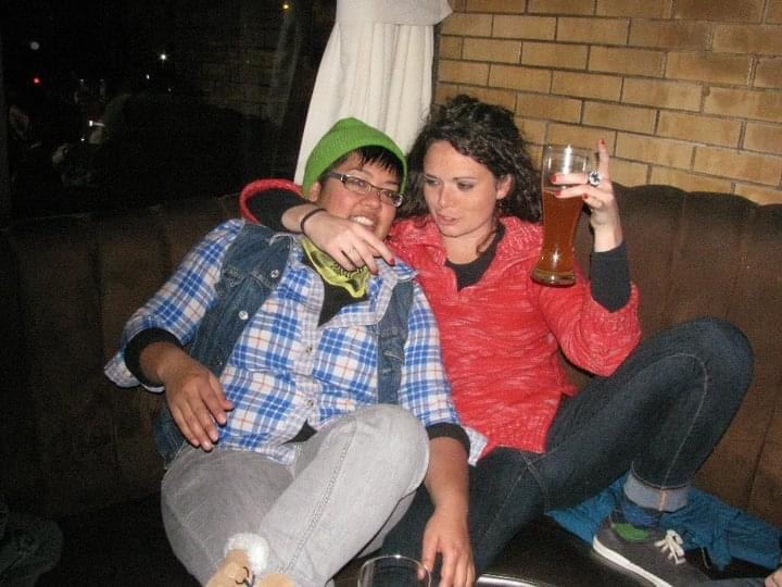 kamala and her friend amy sitting on a bench in a bar drinking beer. kamala is in an outdated flannel, demin vest and green beanie.
