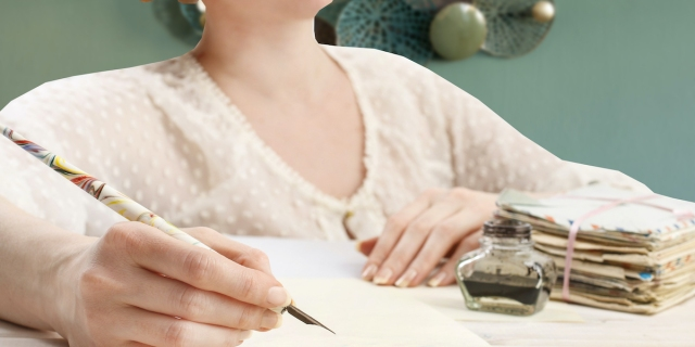 A woman in Victorian period dress sits writing a letter with a fountain pen