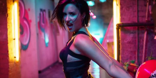 Demi Lovato in a music video, singing towards the camera in pink and blue lights
