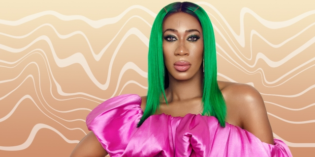A portrait of Mila Jam wearing bright green center-parted hair with hot pink bobby pins and a pink taffeta one-shoulder top with a dramatic ruffle