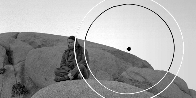 Pauline Oliveros is seated with eyes closed in a meditative pose on an outcropping of large, smooth rocks in a grainy black & white photo that looks like it was taken decades ago, when Oliveros was a young woman. The symbol of a perfect circle with a small dot in the center is superimposed over the photo.