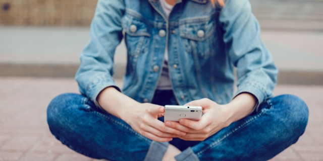 a seated person in dark wash denim jeans cuffed at the ankle and a denim jacket scrolls through their phone