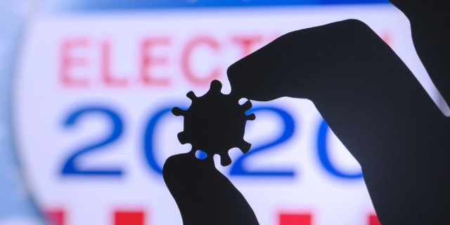 A close-up backlit hand holds a tiny model of a COVID-19 virus against a backdrop that reads ELECTION 2020.