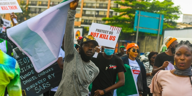 "A photo of protesters in Nigeria with signs that read ""Protect Us, Not Kill Us"" and referring to ending SARS"