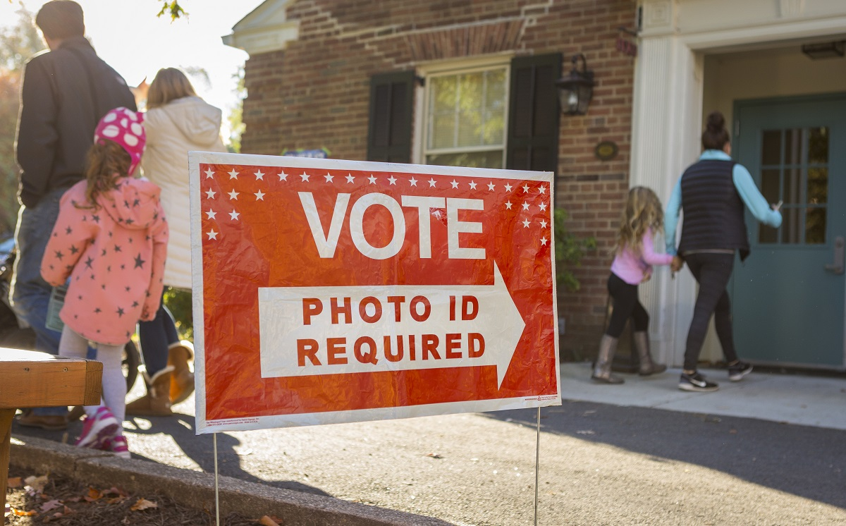 """a red sign outside of a building that reads """"VOTE: photo ID required"""""""
