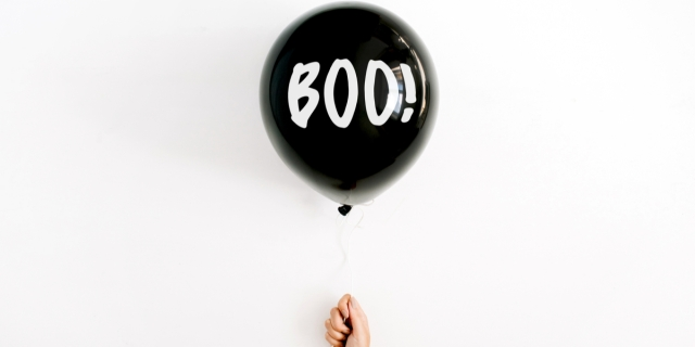 A disembodied hand holds up a floating balloon that reads BOO! against an empty white field