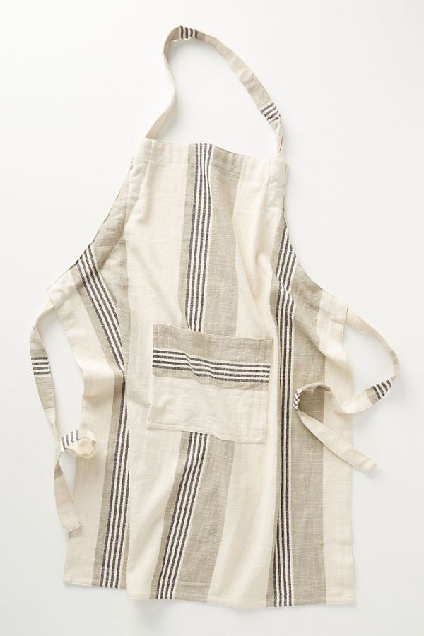 A multicolored stripped apron in cream and shades of grey.