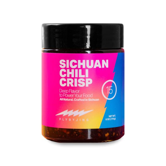 A small bottle of Sichuan Chili Crisp spices with a bright multicolored neon pink label.