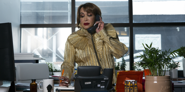 A transfeminine executive using the phone in her office with pen