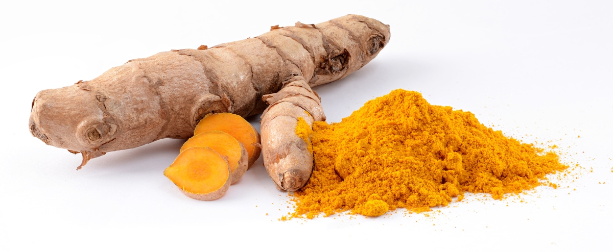 a turmeric root with some sliced pieces and a mound of turmeric powder