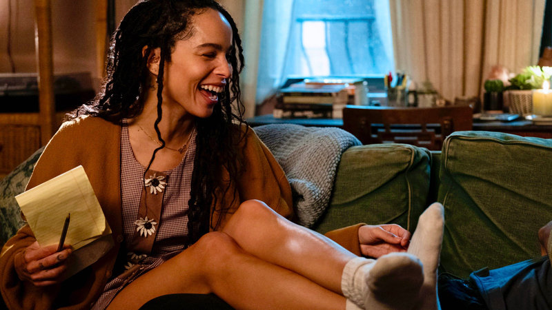 Rob (Zoe Kravitz) laughing on the couch in High Fidelity