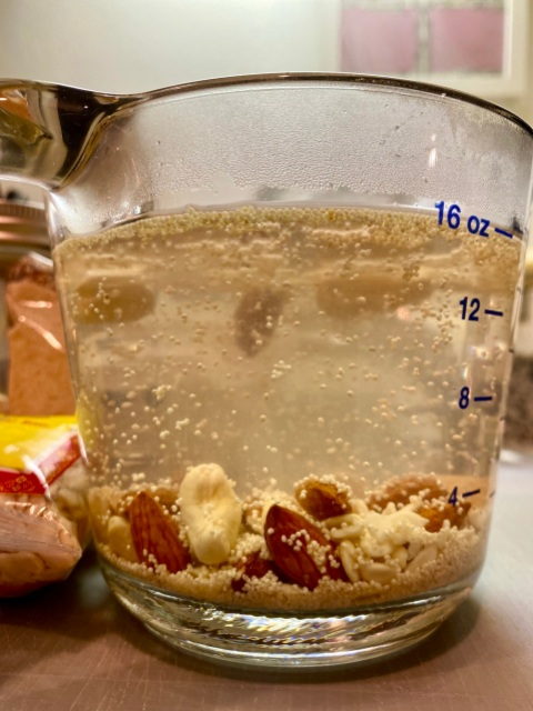 a glass measuring cup full of water with nuts and seeds floating in it