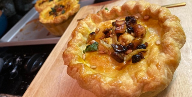 a small korma chicken pot pie that looks like a golden crown, topped with fried herbs and nuts