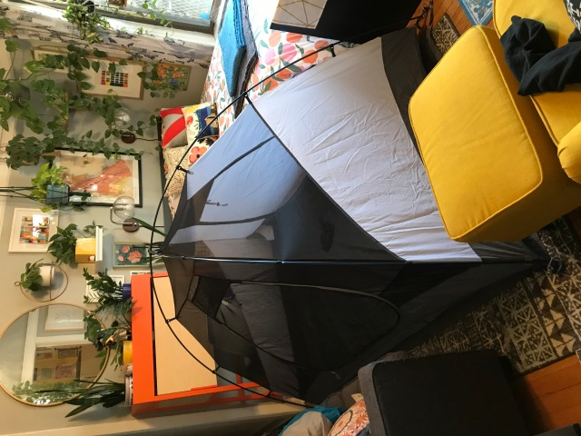 A tent constructed in a cramped living room.