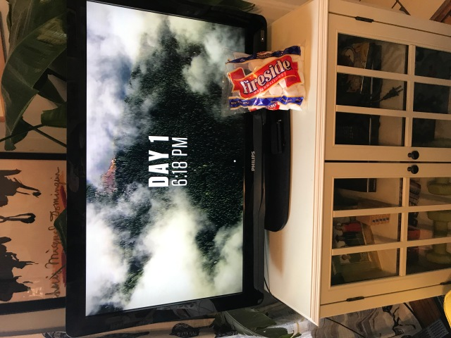 A bag of marshmallows propped up against a tv screen showing an outdoors reality show.