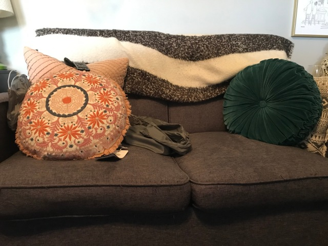 A brown couch with a blanket and a few throw pillows.