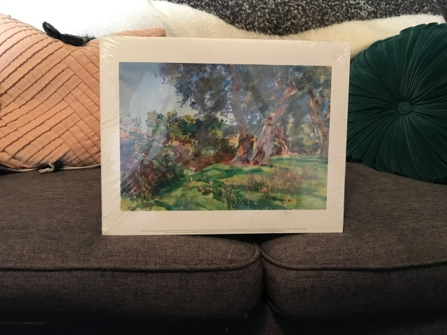 A brown couch with a blanket, a few throw pillows and an Impressionist landscape painting on it.