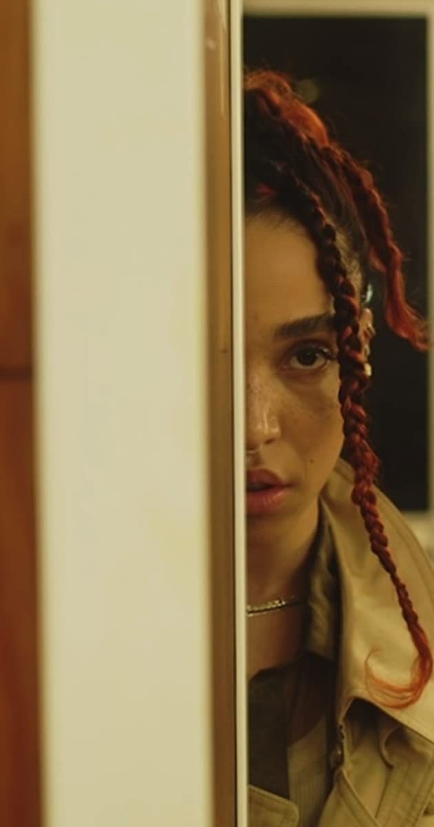 """A still of FKA Twigs with braided red tinged hair standing behind a wall revealing only half of her face. The Still is from her music video """"Sad Day"""""""