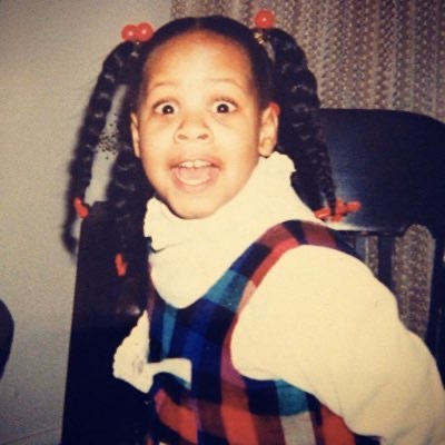 a young Black kid with braids and dressed in a plaid dress with a collar looks into the camera with wide open eyes and mouth partway open