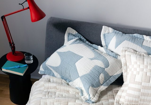 Quilted pillow shams with a graphic white pattern on light blue