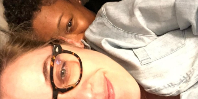 A close up selfie of Lauren Morelli laying in bed as the little spoon, with her wife Samira Wiley cuddling behind her as the big spoon. Samira's face is visible just behind Lauren's ear.