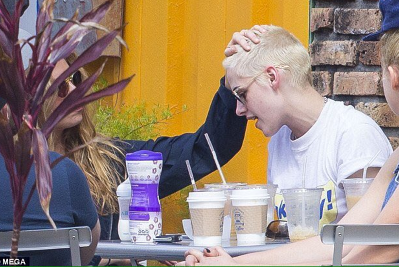 Seated at an outdoor dining table, Stella Maxwell rubs Kristen Stewart's buzzed blonde head.