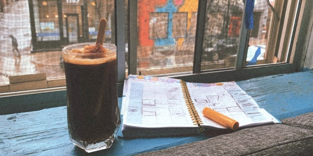 An image showing a glass filled with ice coffee and an ice cream bar. Next to it is a full calender and the background is a city street through the view of a window.