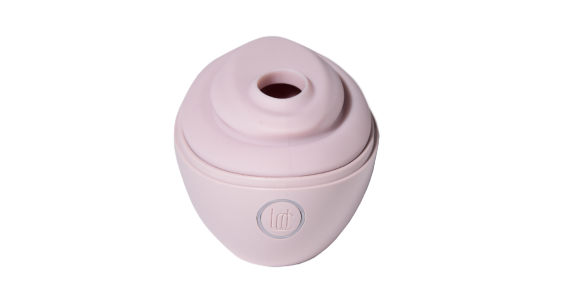 a pink suction toy that looks a little like a short travel cup with the lid on but the drinking hole open, but in a sex toy way