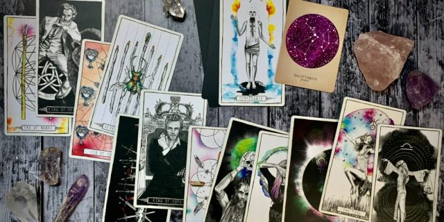 A photo of a scattered deck of Tarot cards and crystals across a distressed wood table