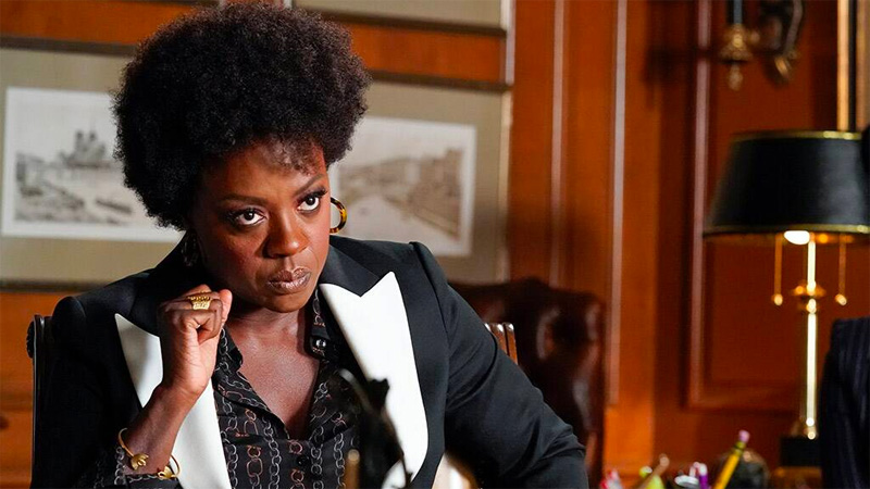 Annalise Keating sits at her desk looking powerful and in charge in a blouse and tuxedo jacket