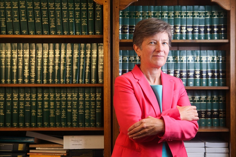 Mary Bonauto, Esq., Civil Rights Director at GLAD poses in front of a legal bookshelf in a pink blazer with her arms crossed.