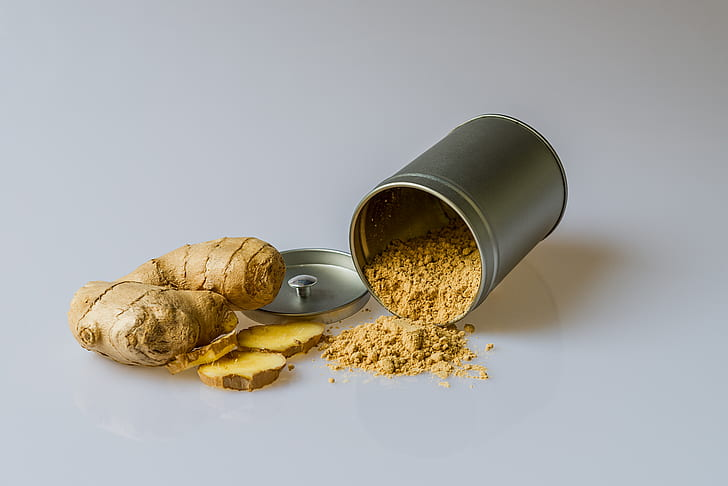 a whole ginger root with some pieces sliced off next to a fallen canister of ginger powder with its contents spilling out