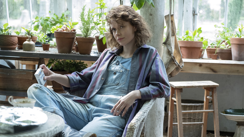Jamie sits in a chair in her garden in The Haunting Of Bly Manor