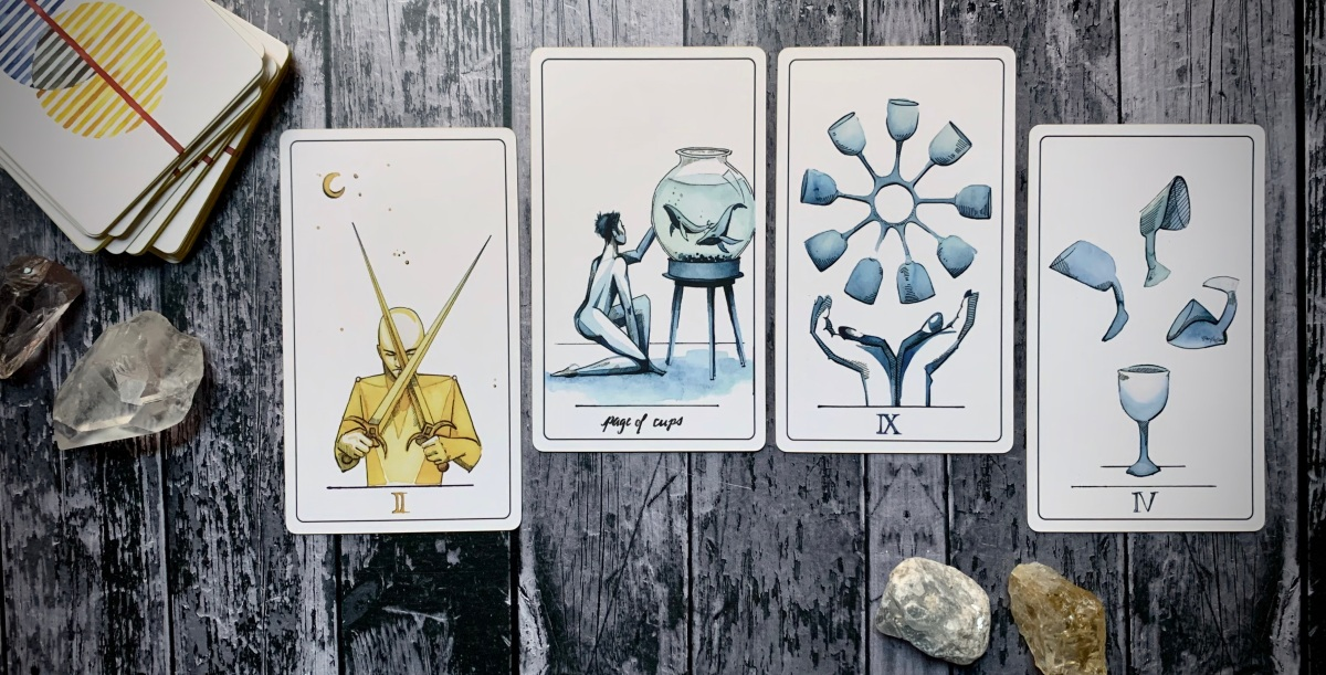 From left to right, cards drawn are: The 2 of swords, page of cups, 9 of cups, and 4 of cups