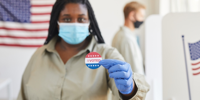 "a black woman in a blue mask and gloves holds up a sticker that says ""I voted"""